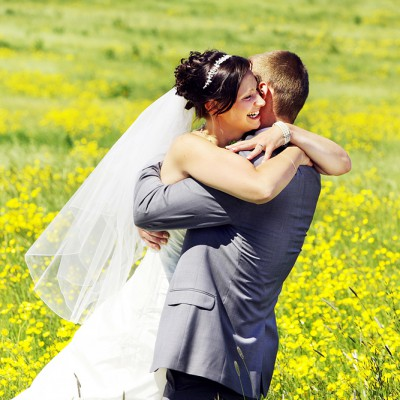 A wedding couple embrace in a field of buttercups.
