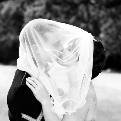 Wedding couple embrace and kiss with her veil pulled over their faces.