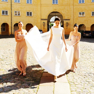 Bride walks across a wide castle courtyard with bridesmaids holding up her dress.