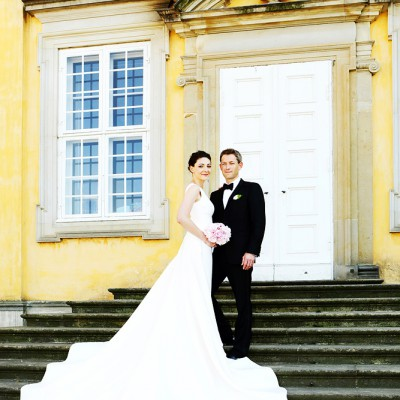 A wedding couple stand on a long set of steps infont of a Danish castle with her flowing dress spread out.