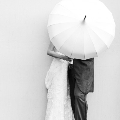 A wedding couple hide from the rain under an umbrella, monochrome.