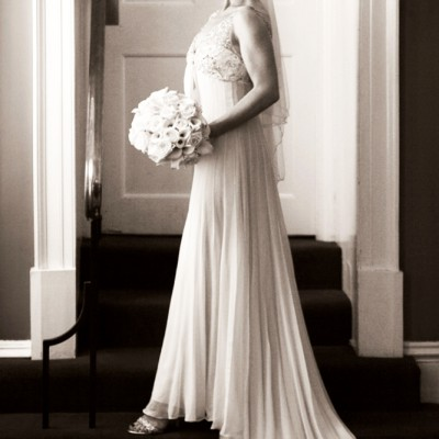 Beautiful elegant bride in sepia stands in a doorway with light from a window to the left.