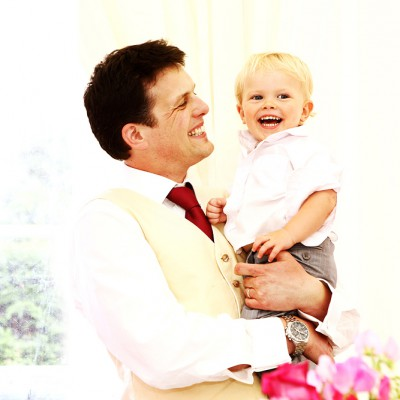Happy groom holds his laughing son in bright marquee.