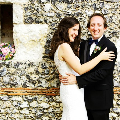 A happy couple laugh as they lean against a flint wall with the bouquet slotted into a reccess.
