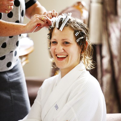 A bride smiles as she chats whilst the hair stylists work on her.