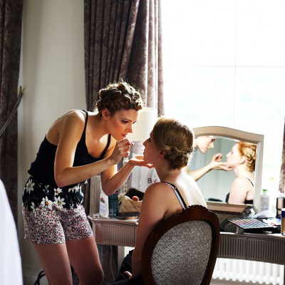 One bridesmaid sits at a mirror whist another helps do her make-up.