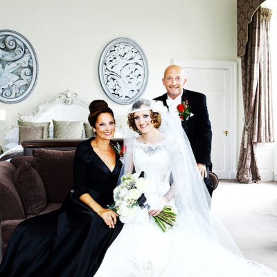 Bride sits in her room waiting to go to ceremony with her proud parents.