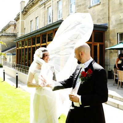 The breeze catches the brides veil as the couple stand in the garden of a country house.