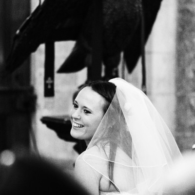 Bride smiles in church with eagle in background.