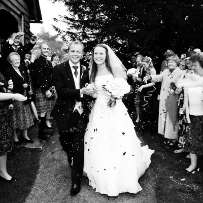 Couple walk arm in arm from the church with guests throwing confetti, monochrome
