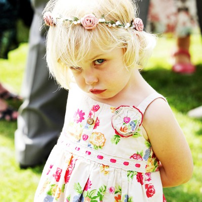 Little wedding girl with flowers in her hair scowls at camera.