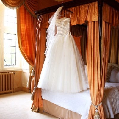 Wedding dress hanging from a four-poster bed with window behind.