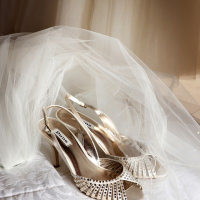 Wedding shoes and veil on bed with shaft of light.