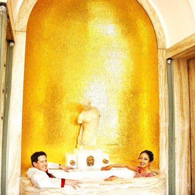 Bride and groom sit clothed in the golden bath at Eltham Palace.