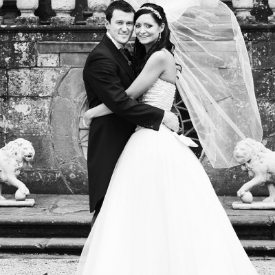 Wedding couple embrace in front of Clearwell Castle with veil blowing in the wind, monochrome.
