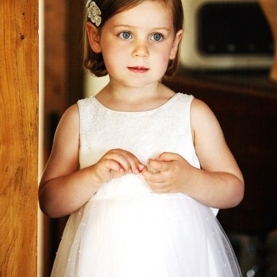 A little bridesmaid waits by the door.