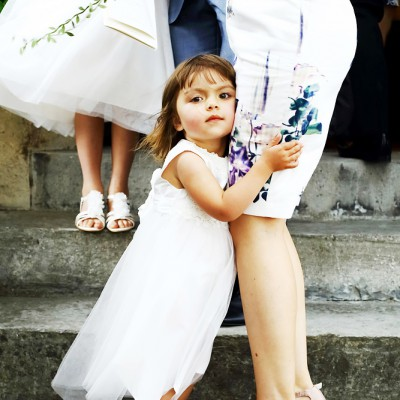 Little girl holds on to her mother's dress on the church steps.