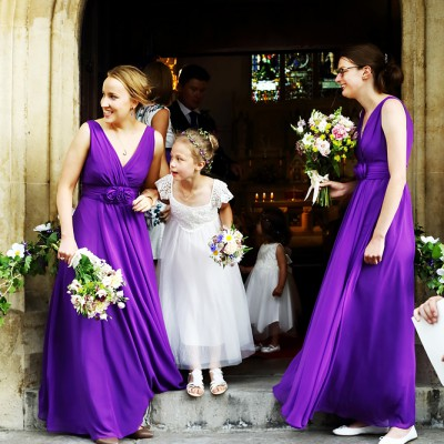 Bridesmaids waiting at the church door look out for the bride.