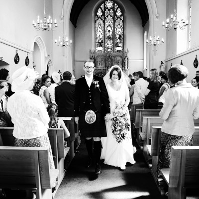 Newly weds walk down the aisle after the ceremony, monochrome.