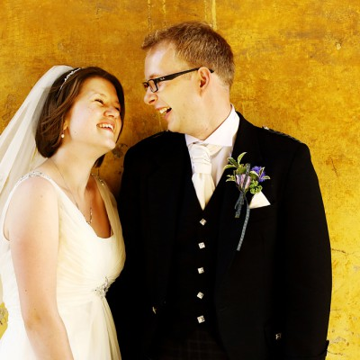 Newly weds smile at eachother against an ochre wall.