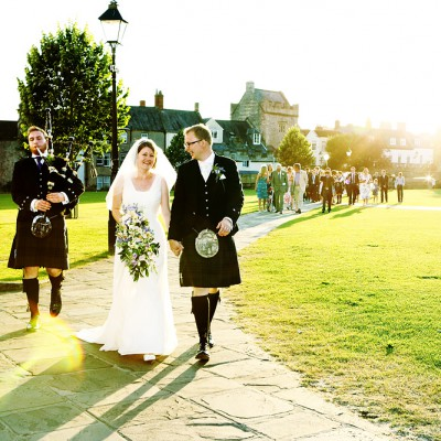 Wedding party walk across Wells Cathedral grounds with Scottish piper.