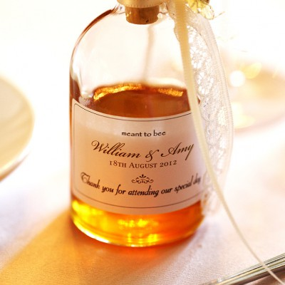 Honey pot gift on table at wedding reception.