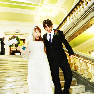 Just married couple walk down the stairs in Islington Town Hall.