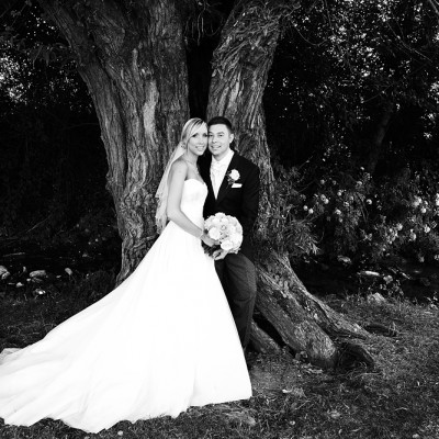Wedding couple embrace leaning against a tree, black and white.