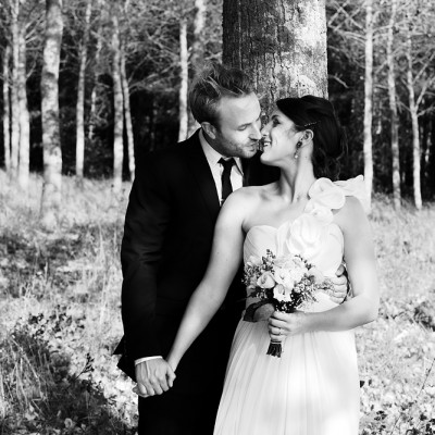 Newly weds share a kiss in a forest, black and white.