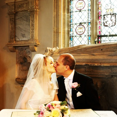 Wedding couple kiss after signing the register withchurch stained glass behind.