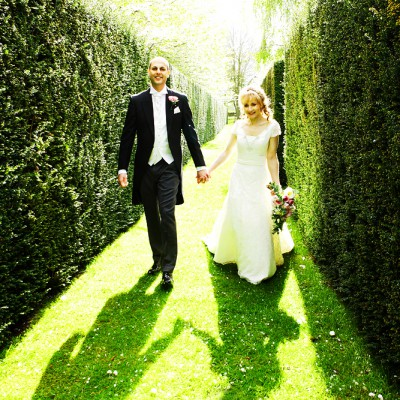 Wedding couple walk hand in hand through maze casting long shadows.