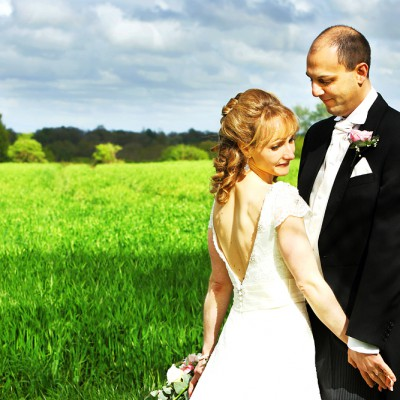 Newly weds hold hands with green field behind.