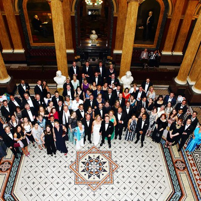 Group shot of wedding party from the upper balcony of the Reform Club.
