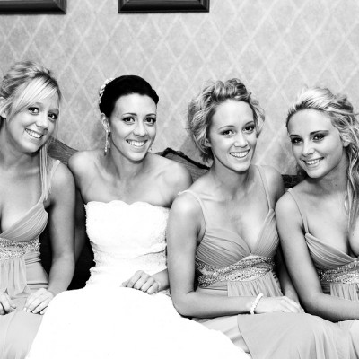 Bride sits on sofa with her bridesmaids, black and white.